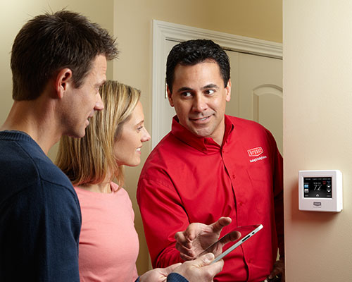 technician discussing thermostat options with homeowners